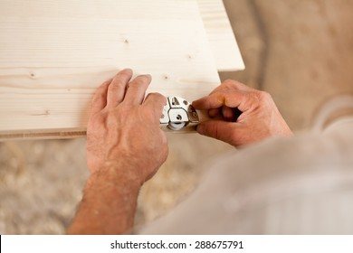 hands of a carpenter placing a metallic component on a wooden board that's part of a piece of a hand made furniture
