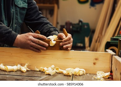 Hands of a carpenter planed wood