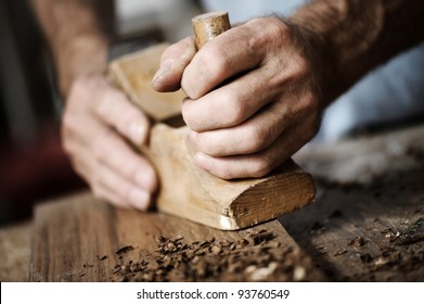 hands of a carpenter planing a plank of wood with a hand plane