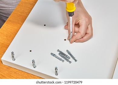 Hands of carpenter is screwing furniture joint connector bolts.
