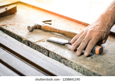 Hands of a carpenter working with a chisel and hammer on wooden workbench