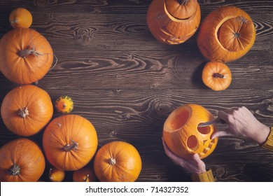 Hands carving jack-o-latern from pumpkin over wooden background, top view, flat lay with copy space for text, toned image