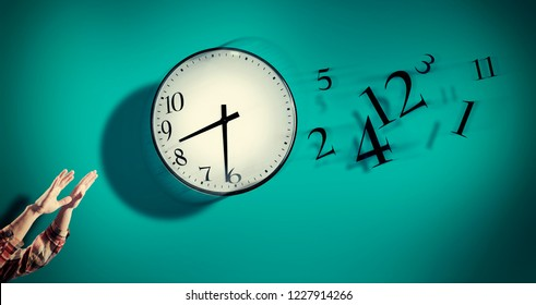 Hands catching a clock with numbers detached in the air. Lack of time concept . The concept of time passing quickly.