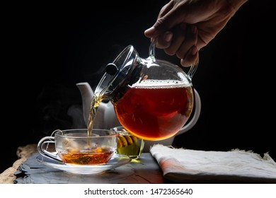 Hands are catching hot tea in the teapot and teacup with steam on reviving the wood and black background.