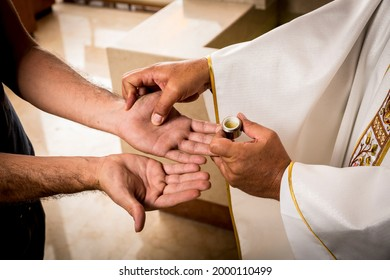 Hands of a Catholic Priest applying the oil for the Anointing of the Sick. Sacraments of the Catholic Christian religion in church.