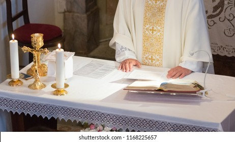 Hands of catholic priest on altar with crucifix, lit candles and gold chalice reading from the holy book