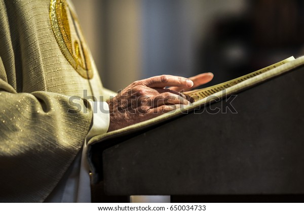 Hands of catholic priest reading a bible.