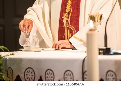 Hands of a catholic priest in red gown on altar, candle in foreground