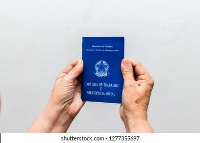 hands of Caucasian senior woman holding work book, Brazilian social security document