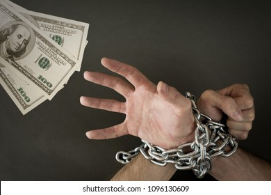 Hands chained together reaches out to the money. Government debt concept