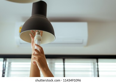 Hands changing with new LED lamp light bulb,Concept save energy and save world