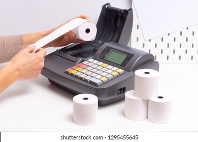 Hands changing roll in Cash Register