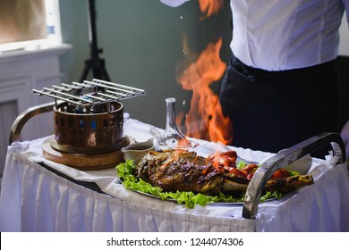 hands chef, burning beef, steak, meat on the bones, a plate of vegetables and herbs. Meat and flambe. Burning steak. Ignites oil