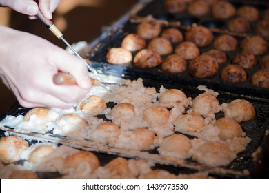Hands of chef cooking Takoyaki ball dumplings or Octopus balls. Takoyaki balls are made with octopus, wheat flour-based batter and pan. Takoyaki is a snack and street food speciality from Osaka, Japan