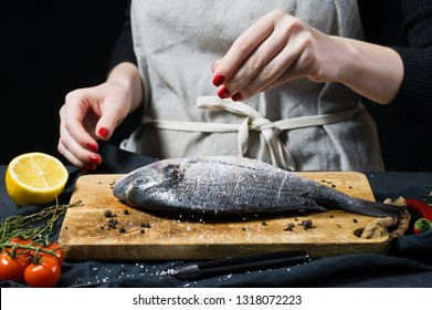 Hands chef salted Dorado fish on a wooden chopping Board, ingredient rosemary, tomatoes, chili, lemon, thyme, pepper, salt. Dark background, side view