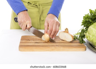 Hands of a chef woman chopping vegetables on a wooden board