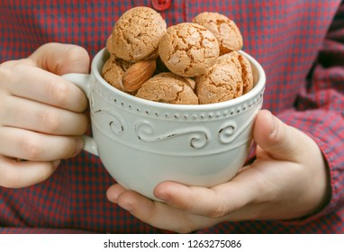 In the hands of the child Cup with Italian almond cookies Amaretti. Crispy Biscuits. Selective focus