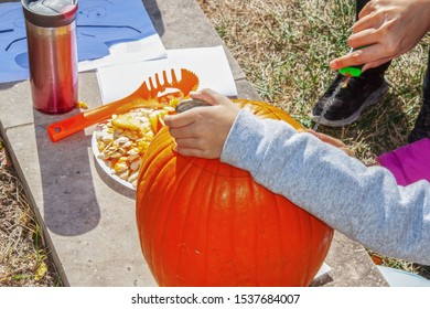 Hands of child cutting out jack-o-lantern from pumpkin with carving knife-holding pumpkin by mouth and working hard at it