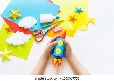 Die Hände des Kindes machen eine Papierhandwerkerrakete. Kosmos Wolken und Sterne gefärbtes Papier. Der kreative Prozess. Kindergarten und Schulentwicklung. Master Class.