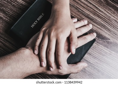 The hands of child and man on the holy bible.