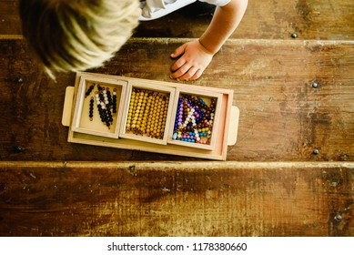 Hands of a child manipulating educational materials to learn to count in a Montessori classroom.