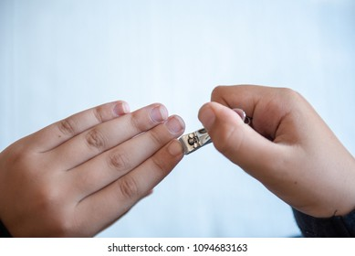 Hands of the child with nail clipper, clipping the nails on his own