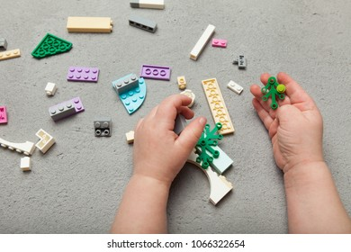 Constructor in the hands of a child on a gray background with a constructor. Fine motor skills.