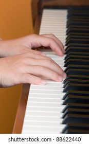 hands of a child on the piano keys