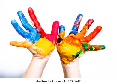 Hands of a child in paint on a white background. A place for a label. A stand-alone subject.