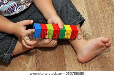 Hands of a child sitting on the floor playing a colored block designer, colorful cubes