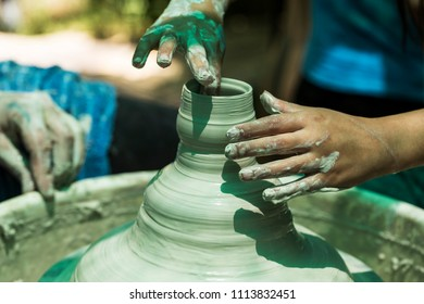 Hands of a child while working with clay on a potter's wheel