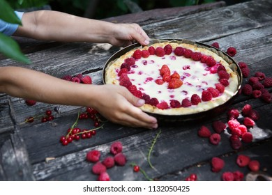 Hands of children decorate berries pie raspberry and currant on a wooden table in a garden