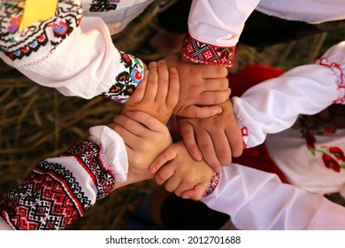 The hands of children in embroidered shirts are intertwined in a welcoming gesture. The united hands symbolize unity. Independence Day of Ukraine, Constitution, Embroidery