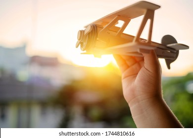 Hands of children holding a toy plane and have dreams wants to be a pilot. Toy balsa wood airplane in the sky, Independence in learning and adventure concept