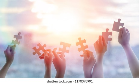 Hands of children students holding pieces of jigsaw together as a symbol for autism or teamwork in school. Happy New Year background.