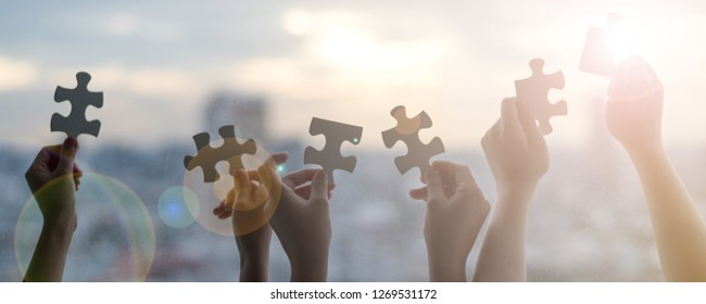 Hands of children students holding pieces of jigsaw together as a symbol for autism or teamwork in school. Happy New Year background concept.