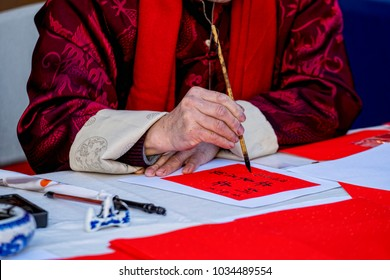 "Hands of Chinese man, writing on a paper. The translation of the Chinese characters is: ""Happy New Year, Happy Year of the Dog""."