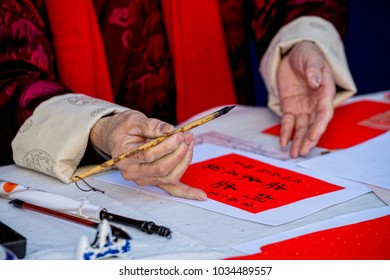"""Hands of Chinese man, writing on a paper. The translation of the Chinese characters is: """"Happy New Year, Happy Year of the Dog""""."""