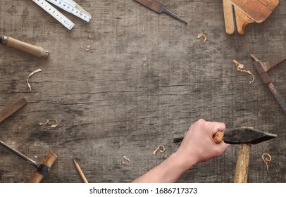 Hands with chisel and hammer on wooden surface. Carving concept with copy space for text or logo. Top view, flat lay composition