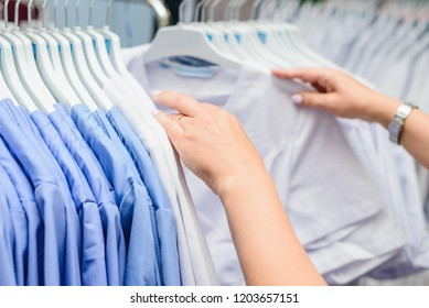 Hands choose a lot of clothes on hangers