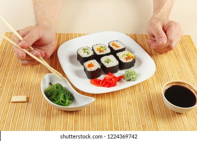 Hands with chopsticks and sushi, hiyashi wakame salad and soy sauce with ginger and wasabi on a bamboo mat.