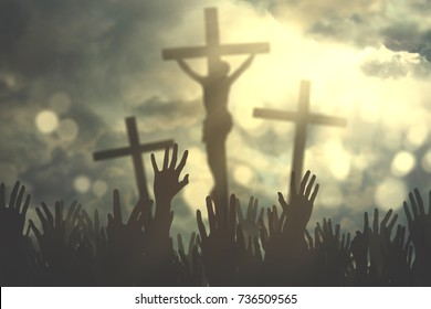 Hands of Christian people praising and praying under three crucifixes at sunrise