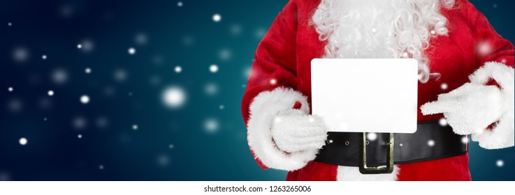 Hands of Christmas Santa with a card on winter background