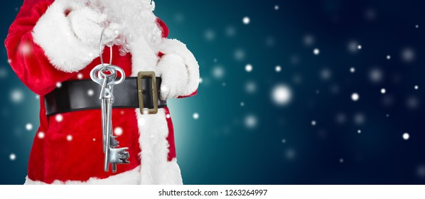 Hands of Christmas Santa Claus with a key on winter background