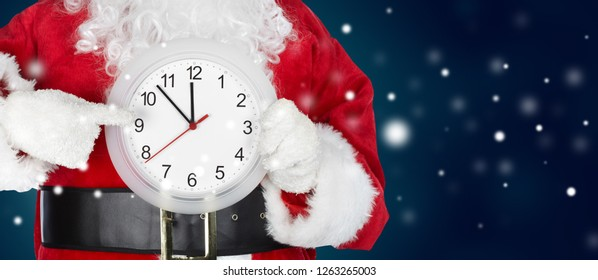 Hands of Christmas Santa with a clock on winter background