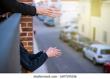 hands clapping on a balcony overlooking a street with the lights on
