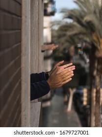 Hands clapping in window for coronavirus doctors