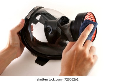 Hands cleaning a black gas mask with a piece of blue cloth