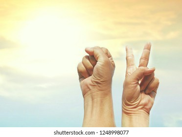 Hands clenched fist and victory sign raising up to the air for okay sign and cooperation concept with sunrise sky background