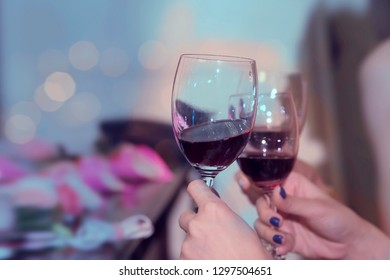 Hands clinking wine glasses a night party.